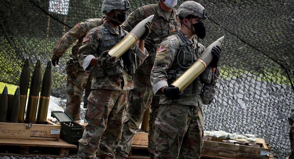 Cadetes da Academia Militar dos EUA (USMA, na sigla em inglês) usam máscaras enquanto esperam para carregar projéteis de 105 milímetros em uma arma de artilharia Howitzer M119 durante atividades de treinamento tático e físico, como parte do Treinamento de Verão de Cadetes em West Point, Nova York, EUA, 7 de agosto de 2020