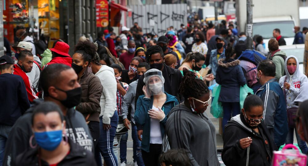 Mulher usando máscara a protetor facial contra coronavírus fala no celular em rua movimentada de São Paulo