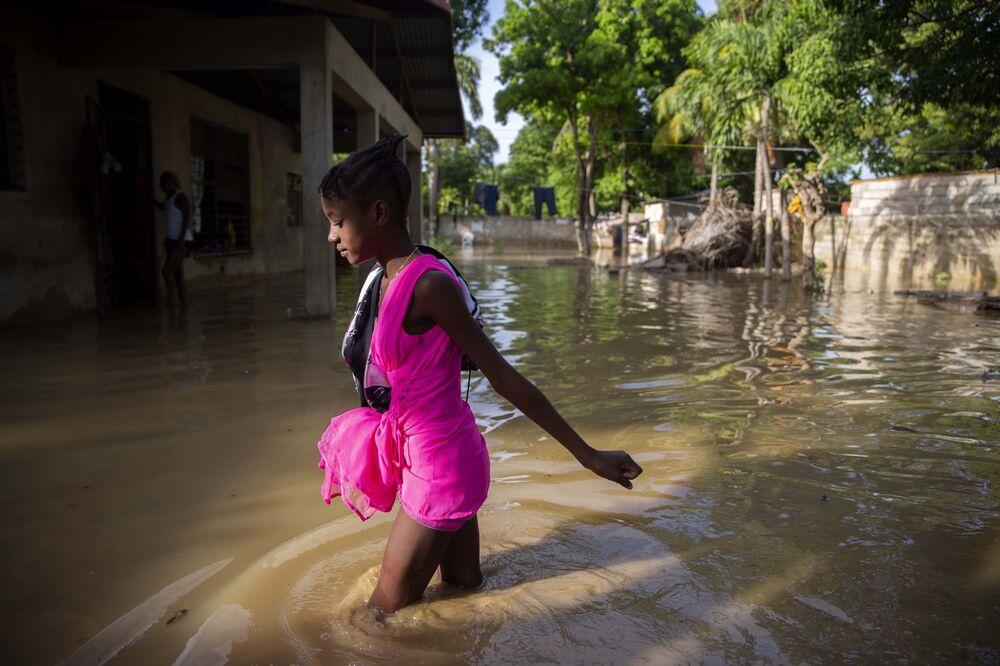 Menina caminha por uma rua inundada no Haiti