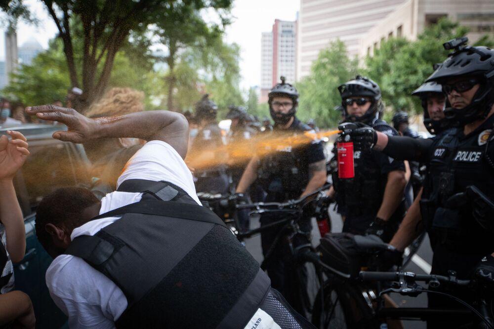 Polícia lança gás sobre um manifestante durante protestos em Charlotte, EUA