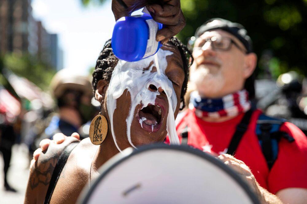 Manifestantes lavam olhos de uma mulher com leite durante protestos em Portland, EUA