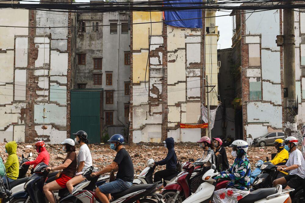 Condutores de scooters em uma estrada alargada em Hanói, Vietnã