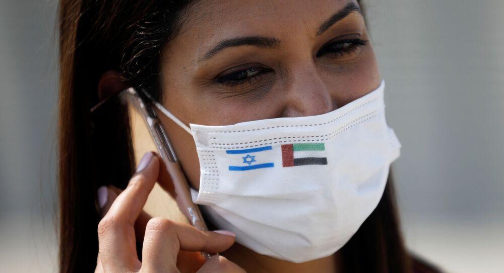 Repórter usa máscara com as bandeiras de Israel e Emirados Árabes Unidos, no Aeroporto Internacional Ben Gurion, Tel Aviv, Israel, 31 de agosto de 2020