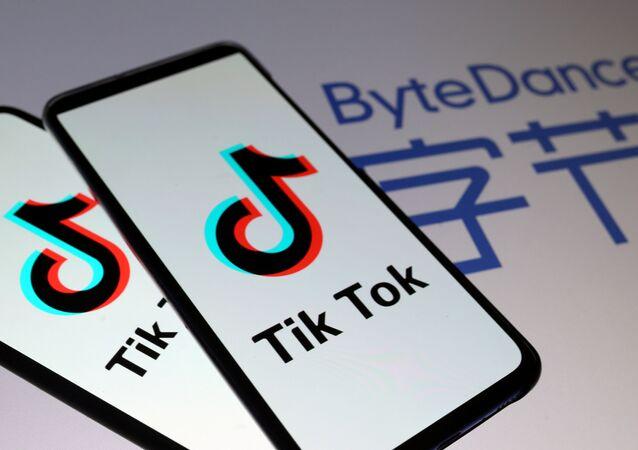 Logotipos da TikTok são vistos em celulares na frente de um logotipo da ByteDance