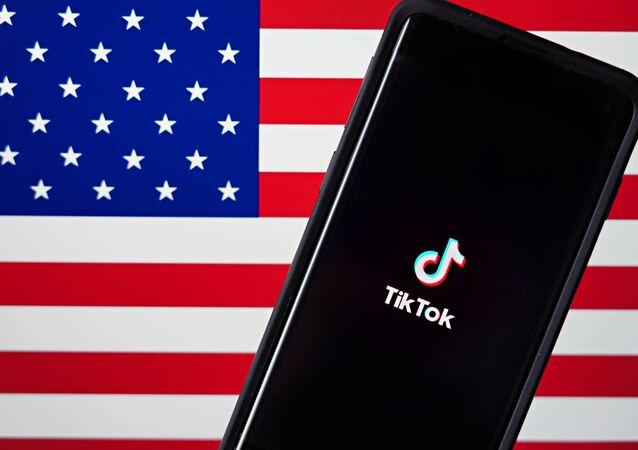Foto ilustrativa mostra o aplicativo TikTok ao lado de bandeira dos Estados Unidos.