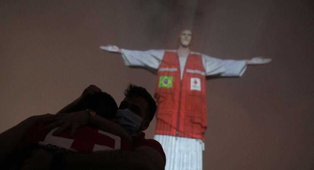 Membros da Cruz Vermelha se abraçam durante homenagem a voluntários que apoiam a sociedade durante a pandemia de COVID-19, Rio de Janeiro, 31 de agosto de 2020