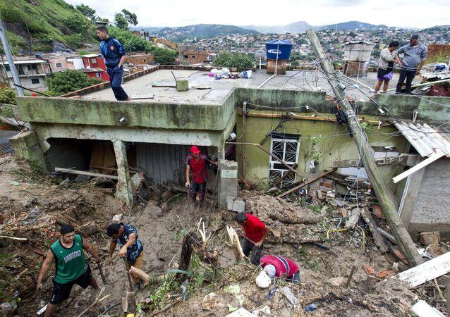 Moradores locais trabalham para limpar a lama e os escombros ao redor das casas destruídas por um deslizamento de terra após fortes chuvas em Vila Ideal, município de Ibirite, estado de Minas Gerais, Brasil, 25 de janeiro de 2020