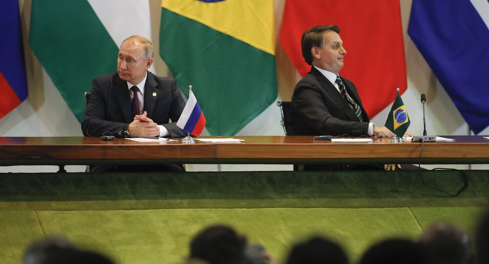 Presidente brasileiro Jair Bolsonaro e o presidente russo Vladimir Putin participam de reunião com membros do Conselho Empresarial e da administração do Novo Banco de Desenvolvimento durante a Cúpula dos BRICS em Brasília, 14 de novembro de 2019