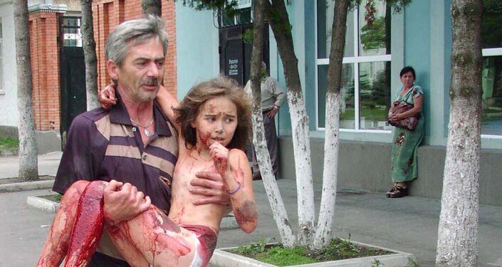 Morador da cidade de Beslan carrega menina feita refém durante ato terrorista para fora da área da escola, Beslan, Rússia, 4 de setembro de 2004