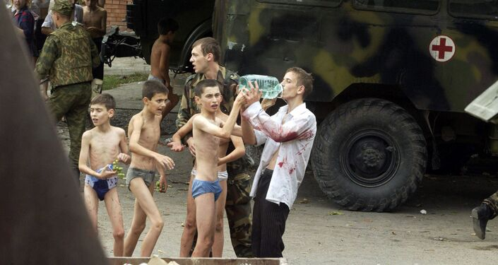 Meninos libertados do cativeiro na Escola Nº1 tomam água, na cidade de Beslan, Rússia, 4 de setembro de 2004
