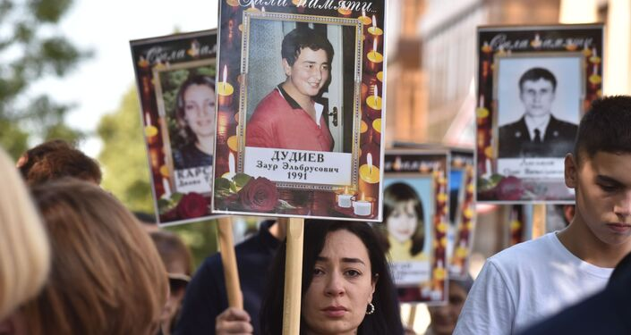 Parentes das vítimas do ato terrorista de Beslan fazem procissão com fotos de seus entes queridos falecidos, em Beslan, Rússia, 3 de setembro de 2019