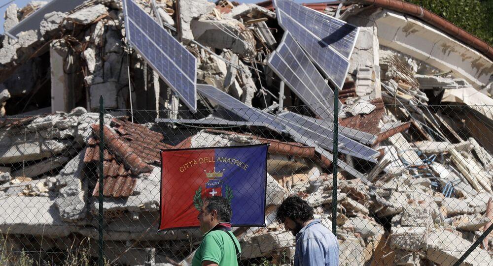 Pessoas passam por um edifício desmoronado em Amatrice, Itália, 24 de agosto de 2017, um ano após um terremoto ter atingido a área e deixado quase 300 pessoas mortas
