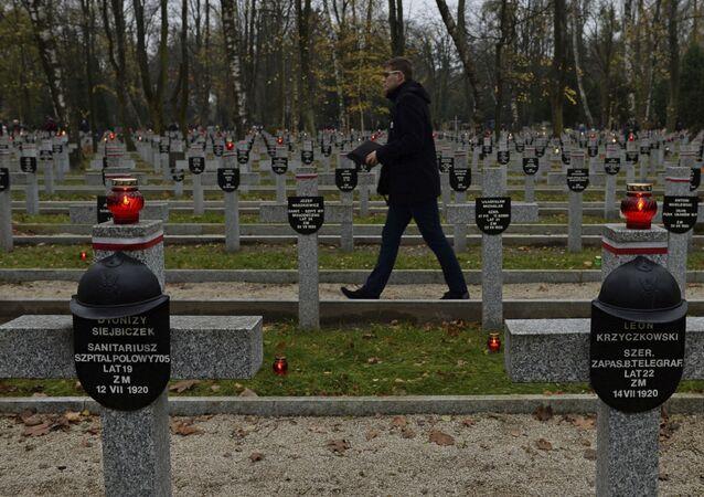 Homem passa diante de cemitério dedicado a soldados poloneses