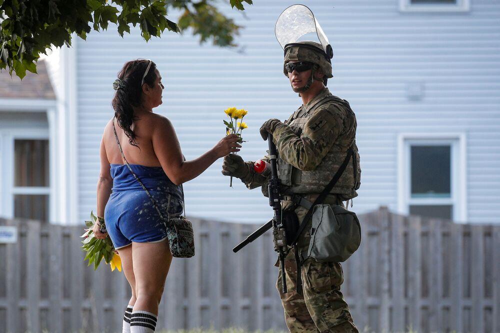 Mulher oferece flores a um soldado da Guarda Nacional durante protestos em Wisconsin, EUA