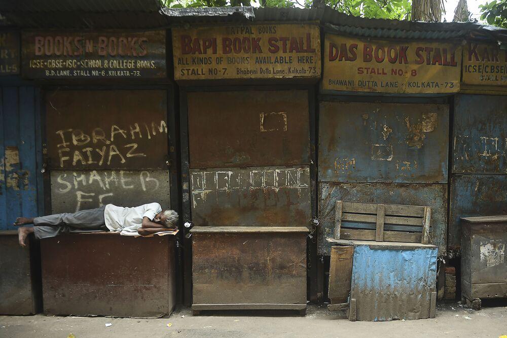 Homem dorme em frente a livrarias fechadas durante o isolamento diurno imposto em meio ao aumento de casos de COVID-19 em Calcutá