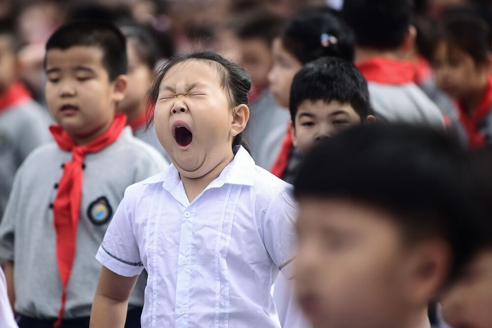 Criança boceja no primeiro dia de escola na China