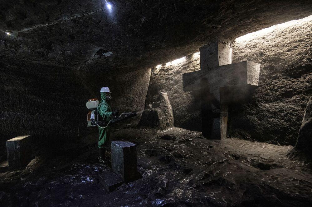 Um trabalhador desinfeta a Catedral de Sal de Zipaquirá, uma igreja subterrânea construída em uma mina de sal