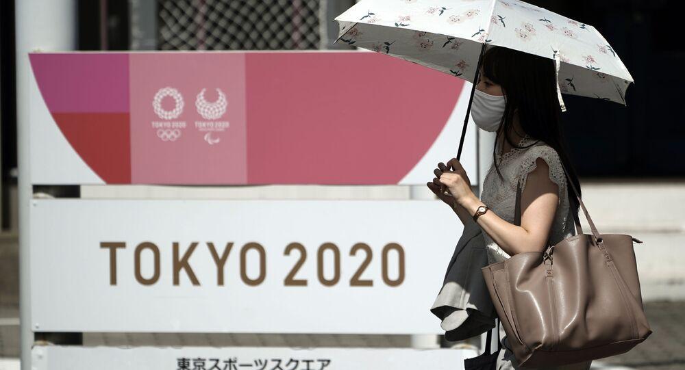 Mulher usando máscara caminham em frente a logotipo dos Jogos de Tóquio 2020, que foram adiados para 2021 devido à pandemia do novo coronavírus