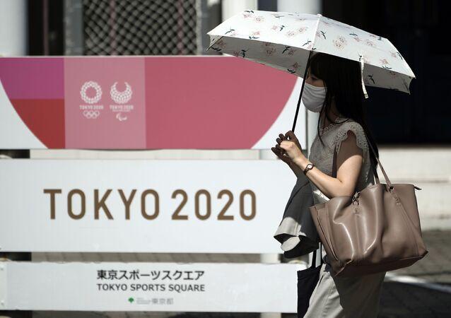 Mulher usando máscara caminha em frente a logotipo dos Jogos Olímpicos de Tóquio 2020, que foram adiados para 2021 devido à pandemia do novo coronavírus.