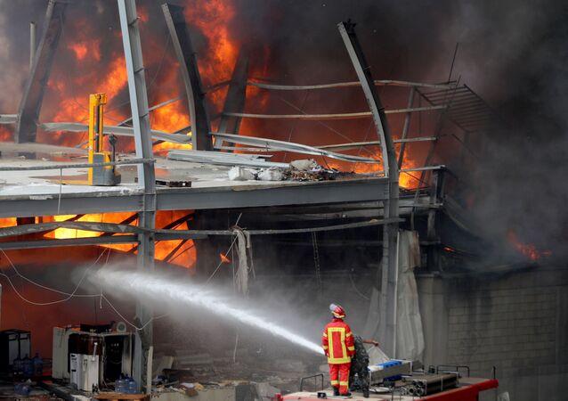 Bombeiro luta contra as chamas que se espalharam por um depósito do porto de Beirute, capital do Líbano