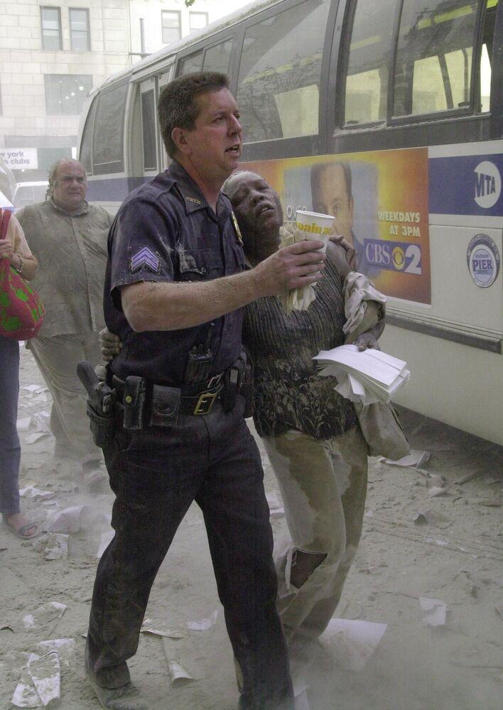 Policial ajuda mulher ferida durante o ataque ao World Trade Center em Nova York em 11 de setembro de 2001