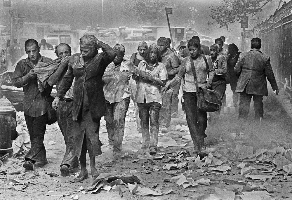 Moradores de Nova York, cobertos de poeira oriunda dos escombros, andam pelas ruas da cidade