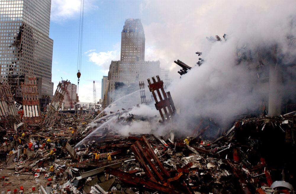 Bombeiros lutam contra incêndio nos escombros do World Trade Center após este ser atacado em 11 de setembro de 2001