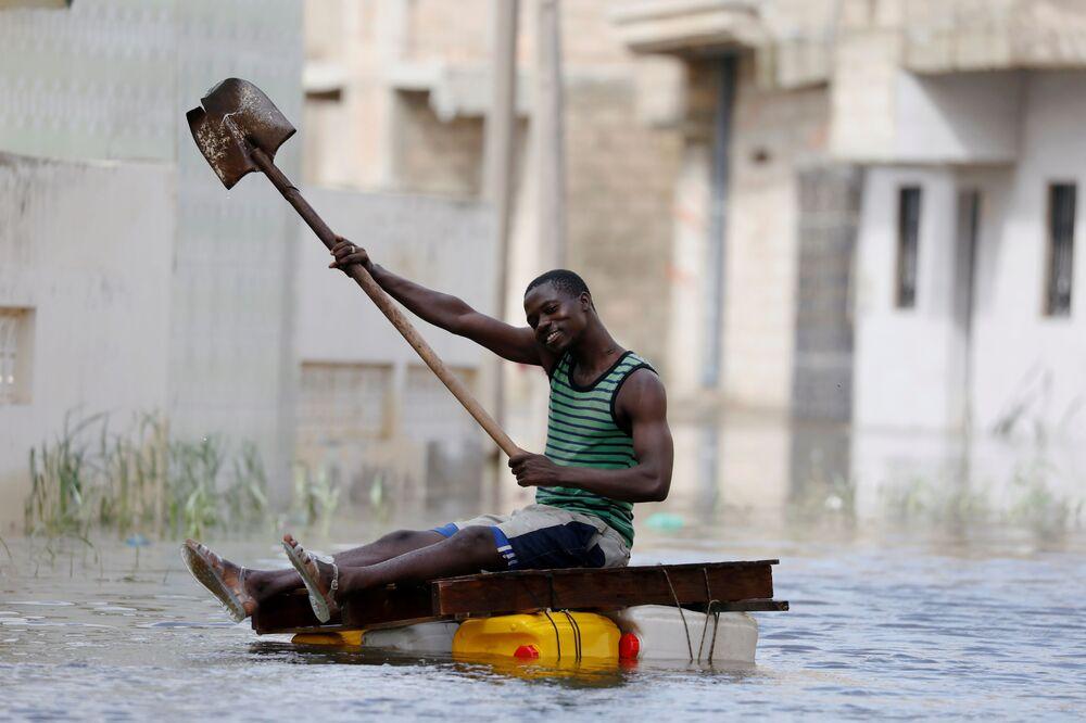 Morador dirige balsa após fortes chuvas no Senegal