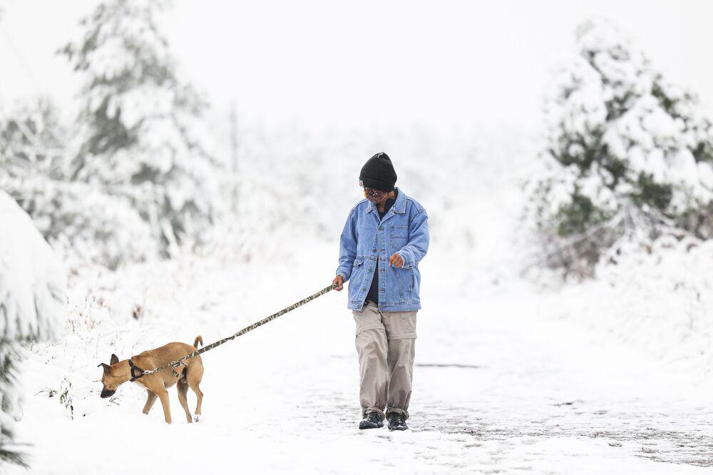 Mulher passeia com cachorro durante nevasca no Colorado, EUA