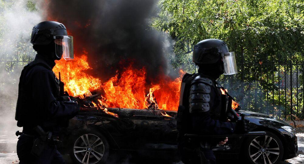 Em Paris, policiais passam em frente a um carro em chamas em meio aos protestos dos coletes amarelos, em 12 de setembro de 2020.
