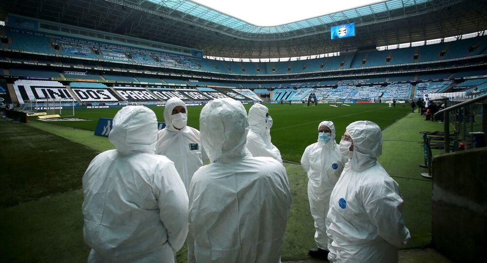 Funcionários usam roupa protetora contra coronavírus na Arena do Grêmio, antes do jogo entre Grêmio e Fortaleza