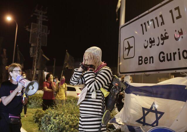 Manifestante com máscara do primeiro-ministro de Israel, Benjamin Netanyahu, participa de protesto no aeroporto Ben Gurion