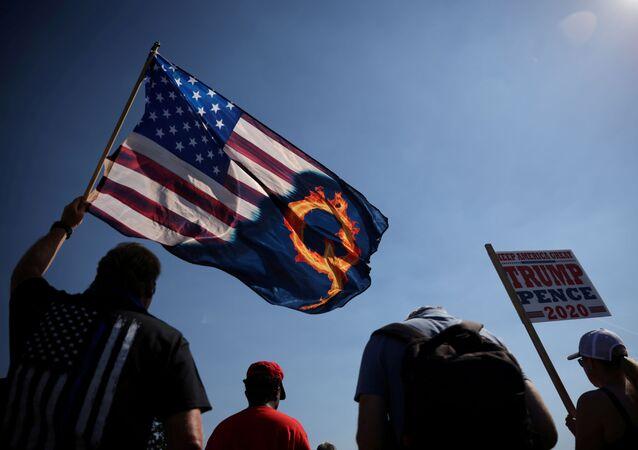 Apoiador do presidente dos EUA, Donald Trump, com bandeira que faz referência à teoria de conspiração QAnon, Cidade do Oregon (EUA), 7 de setembro de 2020
