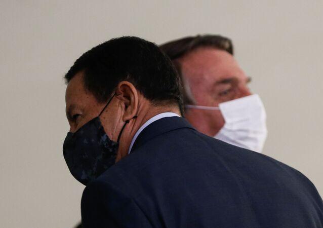 Presidente Jair Bolsonaro fala com o vice-presidente Hamilton Mourão na tomada de posse de Eduardo Pazuello como novo ministro da Saúde