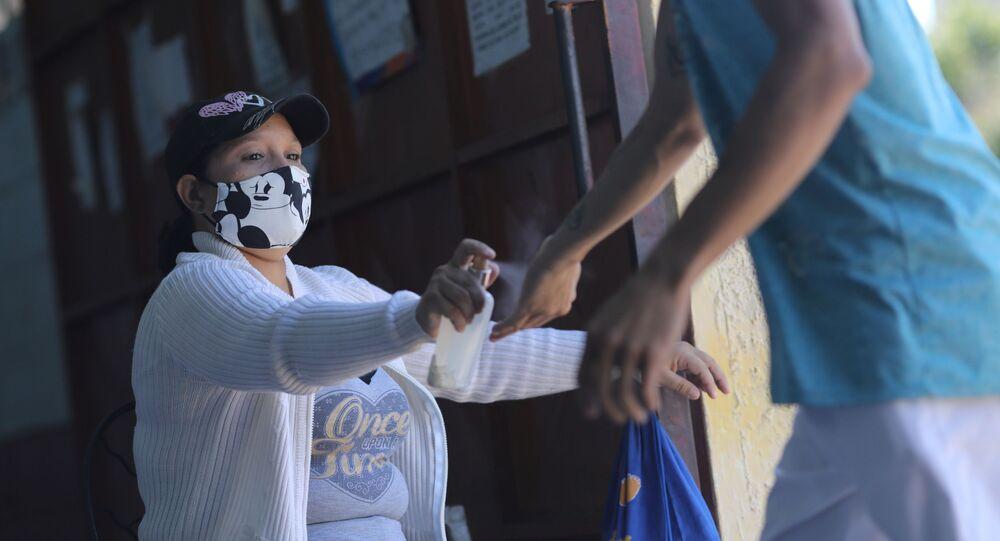 Enfermeira joga spray de álcool para higienizar clientes contra coronavírus em mercado em Caracas, na Venezuela