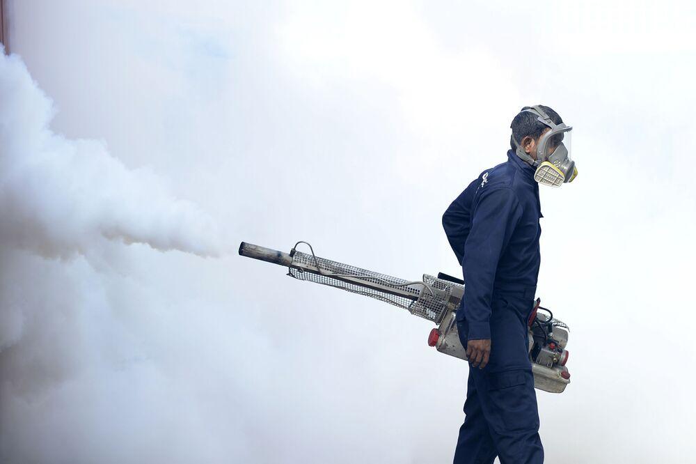 Um trabalhador municipal faz fumigação para matar mosquitos em território de escola em Colombo, no Sri Lanka
