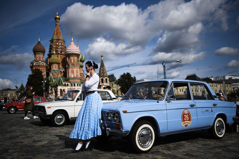 Moça posa perto de carro Zhiguli antes do início do rali de carros da era soviética