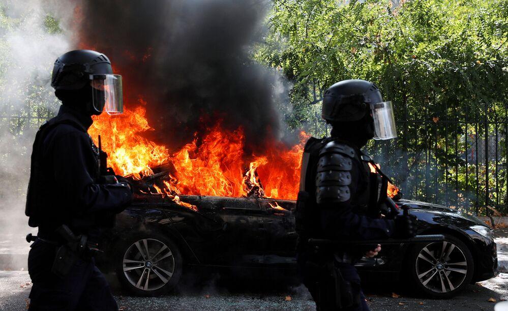 Policiais franceses passam por um carro em chamas durante um protesto dos Coletes Amarelos em Paris