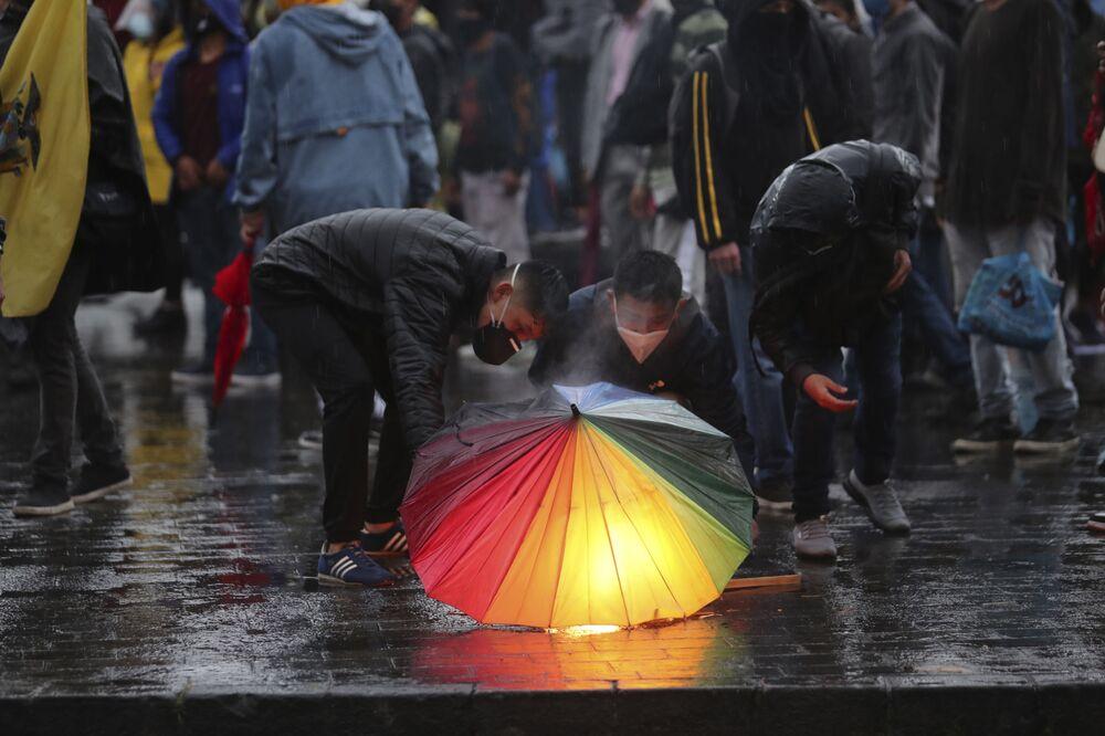 Manifestantes seguram tocha sob guarda-chuva durante um protesto contra política econômica de governo de Equador