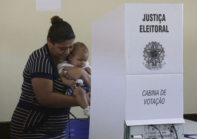 Em Brasília, uma mulher com um bebê nos braços deposita seu voto em uma urna eletrônica durante as eleições gerais no Brasil, em 28 de outubro de 2018.