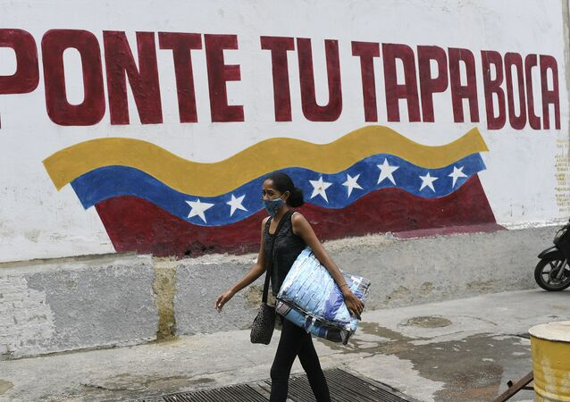 Mulher com máscara contra o coronavírus caminha em Caracas, na Venezuela, em frente a mensagem que diz: 'Coloque sua máscara'