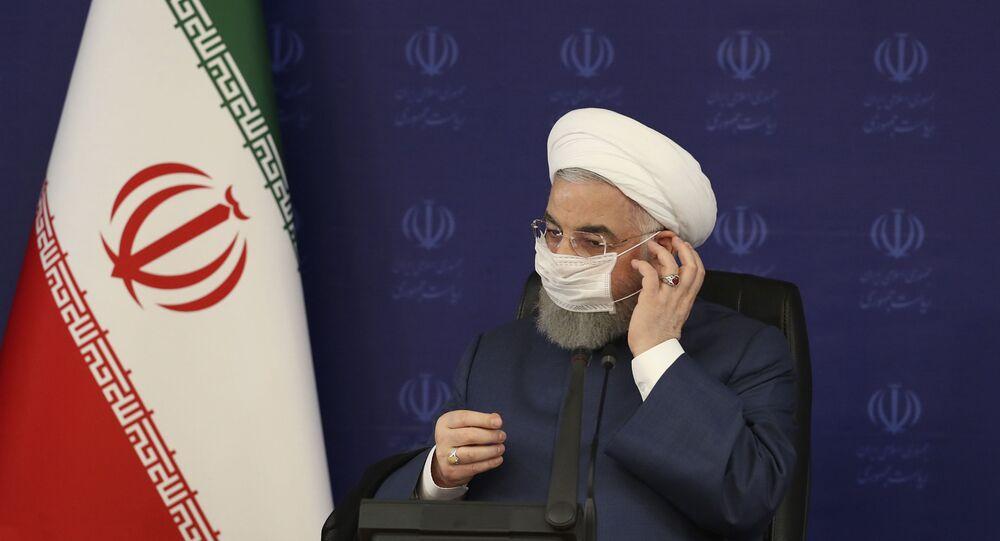 Em Teerã, o presidente do Irã, Hassan Rouhani, ajusta sua máscara em frente a um painel no qual se lê a Presidência, em farsi, durante encontro no quartel-general de luta combate à COVID-19 no país, em 18 de julho de 2020.