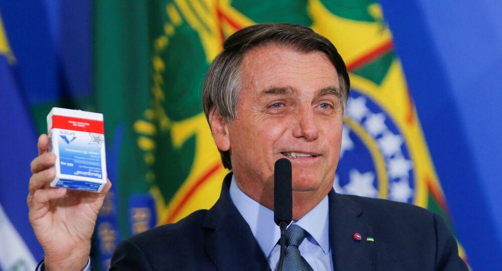 Presidente Jair Bolsonaro expõe uma caixa de hidroxicloroquina durante cerimônia em Brasília