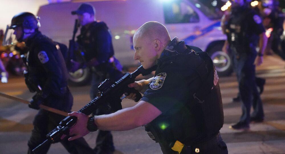 Em Louisville, no estado norte-americano de Kentucky, um policial empunha uma arma durante protestos após a condenação de um agente pelo assassinato de Breonna Taylor, em 23 de setembro de 2020.