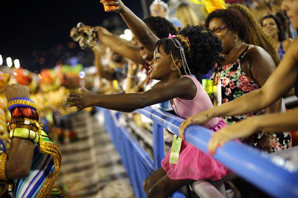 Menina cumprimenta participantes do Carnaval do Rio de Janeiro, 2015