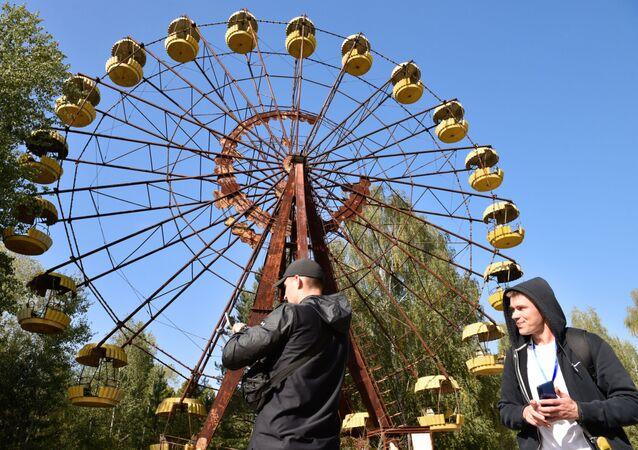Turistas próximos de roda gigante na zona de exclusão de Chernobyl