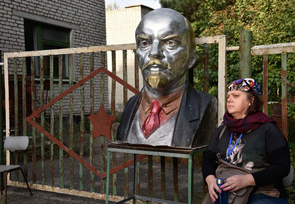 Turista observa busto de Lenin na zona de exclusão de Chernobyl