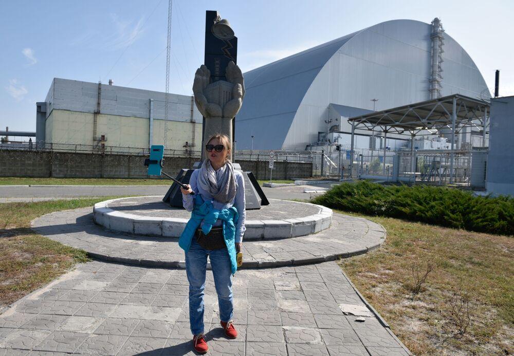 Turista faz selfie com sarcófago do reator, na zona de exclusão de Chernobyl