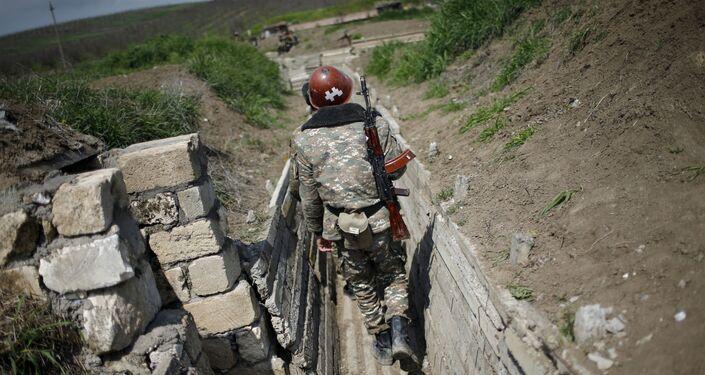 Próximo da região de Nagorno-Karabakh, um soldado armênio caminha em uma trincheira, em 8 de abril de 2016.