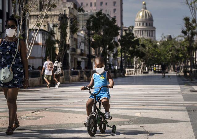 Em Havana, Cuba, uma mulher acompanha uma criança que anda de bicicleta enquanto ambos usam máscaras de proteção devido à pandemia da COVID-19, em 3 de julho de 2020.